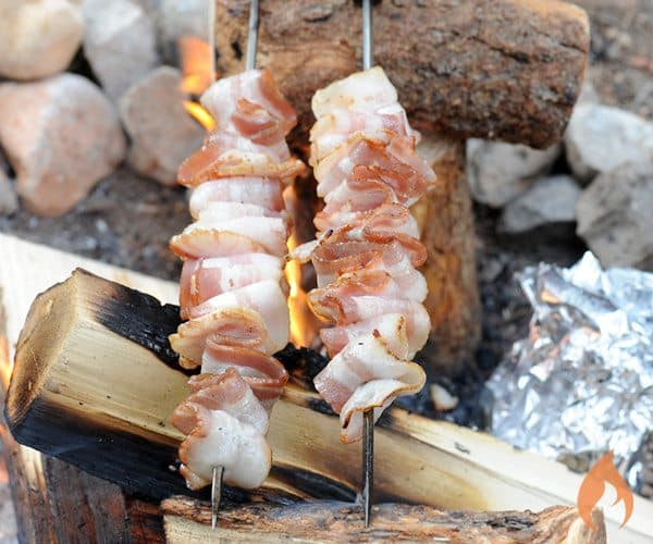 bacon on skewers over campfire