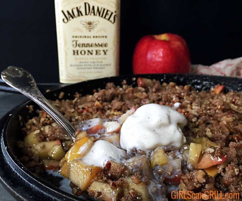 a spoonful of apple crisp coming out of a cast iron pan with melted ice cream