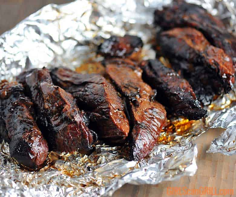 cooked juicy beef ribs lying on foil
