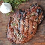 grilled ribeye on a wooden board with garlic nearby