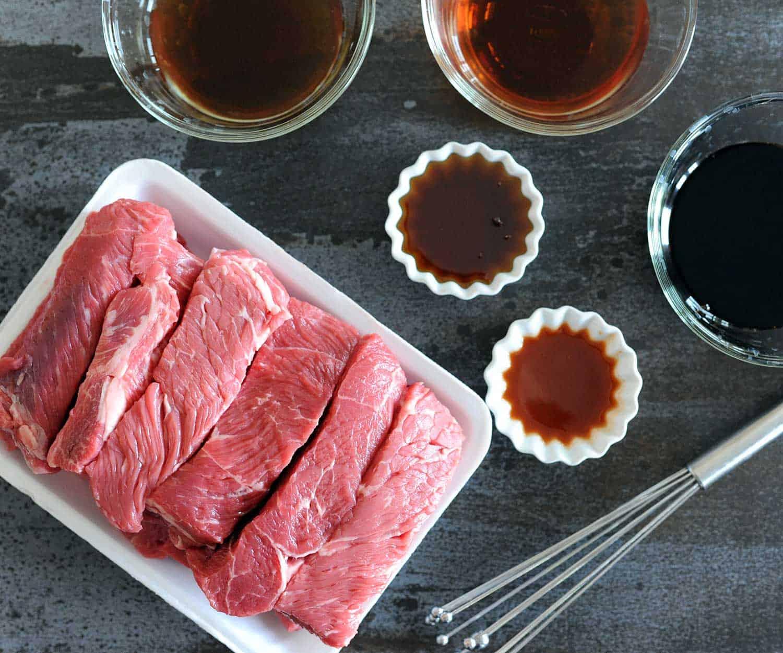 platter of raw boneless beef ribs and marinade
