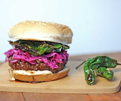burger topped with red cabbage and shishito peppers with white background