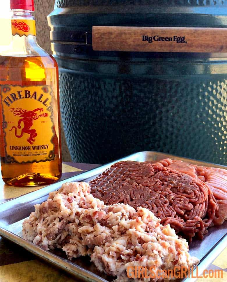 tray of 3 ground meats with fireball whisky bottle near big green egg