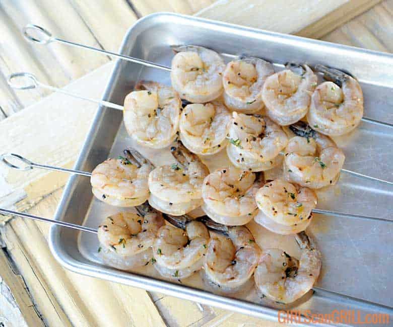 16 shrimp on 4 metal skewers on a pan