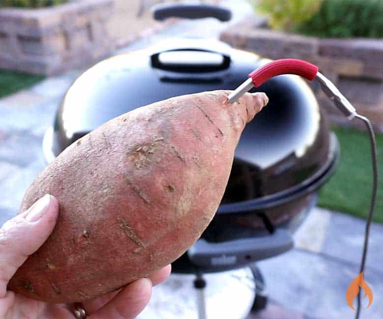 holding a sweet potato with a probe in it in front of a black grill