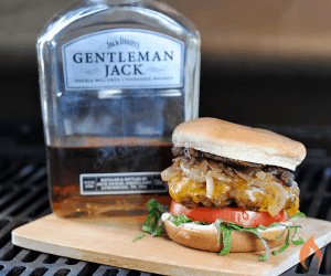 burger on a wood board next to bottle of whiskey