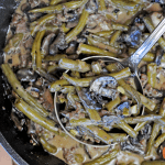 green bean casserole in a cast iron pan with large spoon