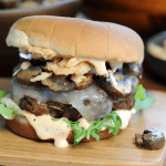 burger on wood board with lettuce, special sauce, mushrooms and onions