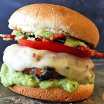 burger topped with tomatoes, white cheese and avacado salsa