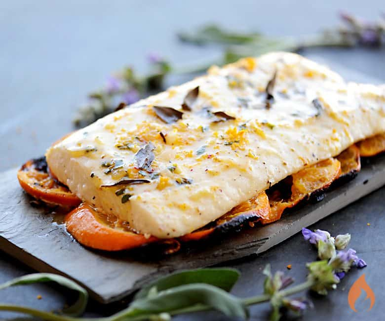 grilled halibut resting on tangarine slices with sage flowers