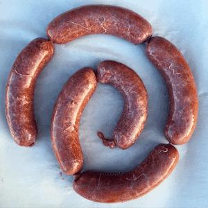 spiral of corned beef brisket sausages on white background