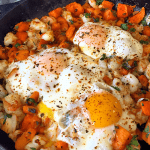 skillet with sweet potatoes and fried eggs
