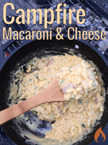 cast iron skillet of macaroni and cheese over a campfire