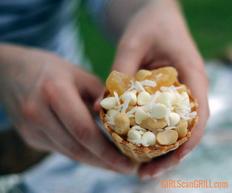 holding a waffle cone filled with nuts and pineapple