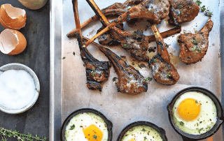 grilled lamb chops on pan with 3 mini skillets of fried eggs