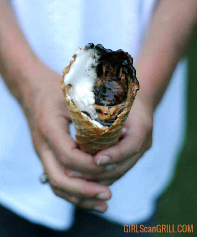 holding an ice cream cone with melted chocolate and marshmallows