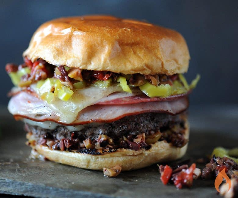burger stacked with ham and olive spread with gray background