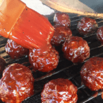 brushing sauce on meatballs on grill