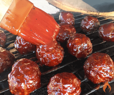 brushing sauce on meatballs on grill