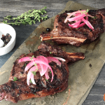 two elk chops topped with pickled red onions on a slate tile
