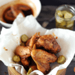 bowl of nashville hot chicken with sauce and pickles on side