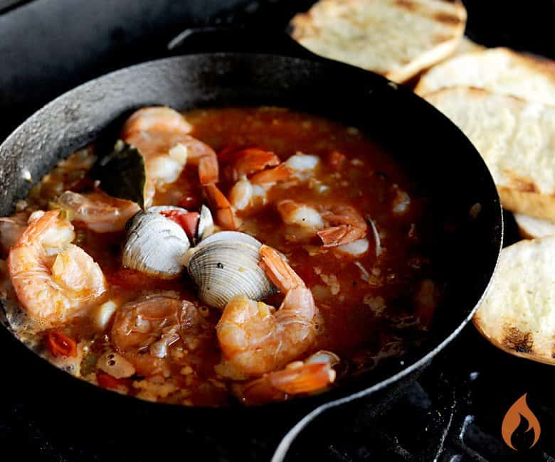 cast iron pot of grilled cioppino with toasted bread