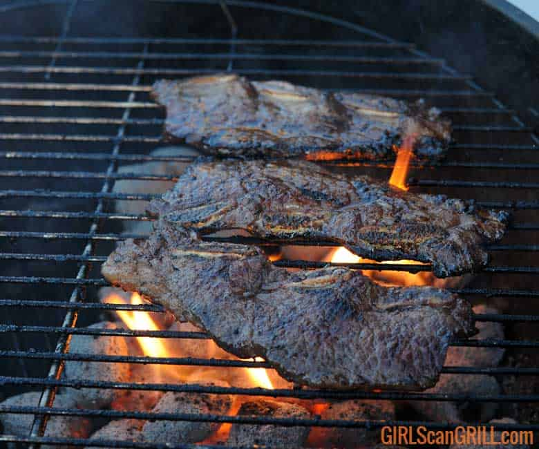 3 kalbi ribs cooking on a grill
