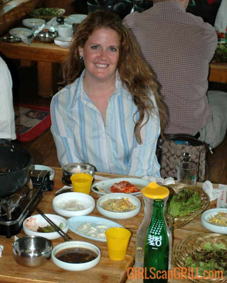 woman sitting at a table with korean food