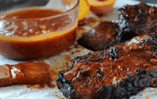pork chops with bowl of peach bbq sauce to side