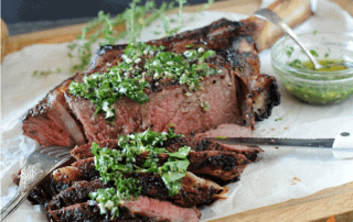 sliced ribeye with bone topped with herb sauce