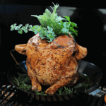 chicken in pan on grill standing up with herbs in top