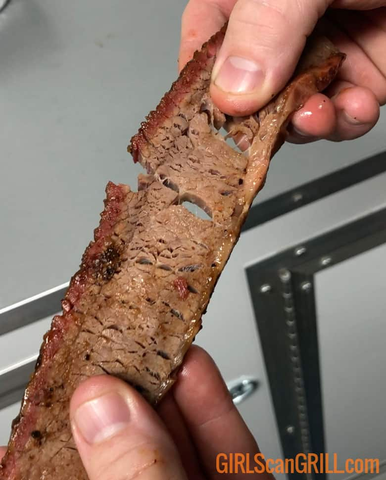 two hands pulling apart a slice of brisket flat
