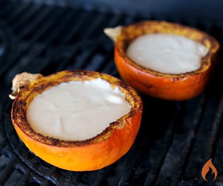 two pumpkin halves on grill with uncooked cheesecake filling inside