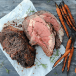 sliced prime rib laying on white paper near grilled carrots