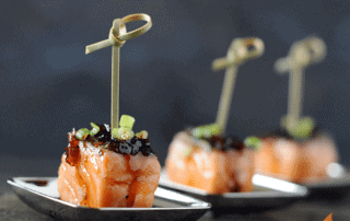 salmon cube on small plate with glaze on top and toothpick