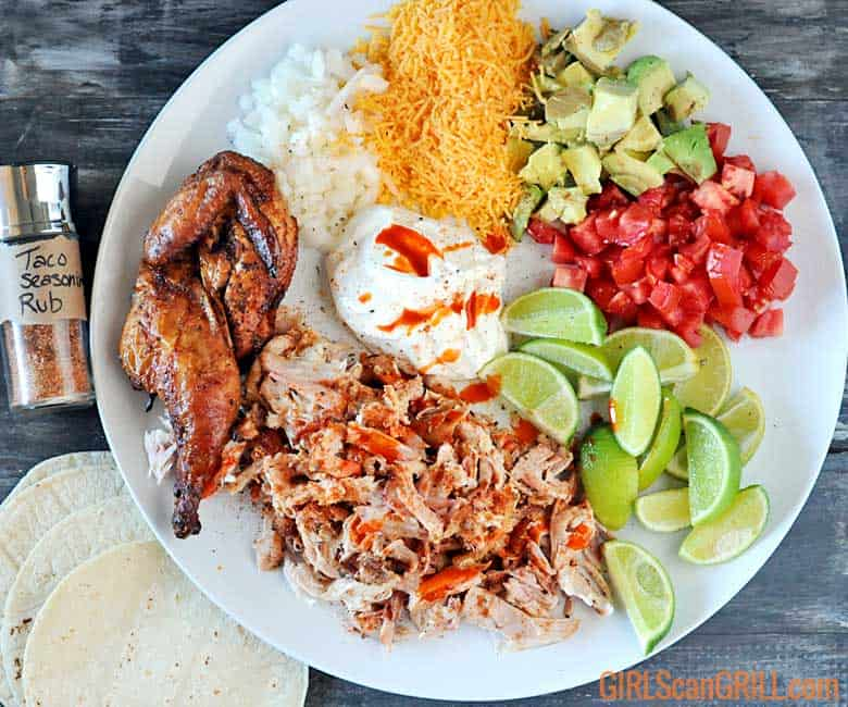 white plate with grilled chicken, cheese, nions, tomatoes, limes, sour cream