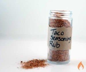 bottle of taco seasoning on white background with some seasoning on table