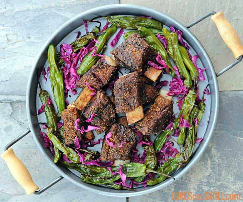 platter of smoked beef short ribs surrounded by peppers and red cabbage