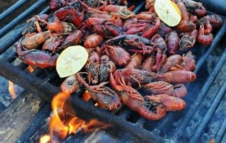 grill grate over campfire covered with crawfish and lemon