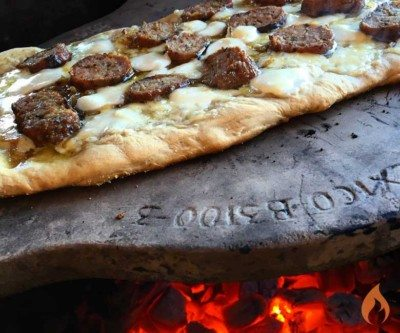 pizza topped with sausage on a ceramic plate over a fire