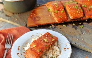 plate of salmon on rice with more filets and rice in background
