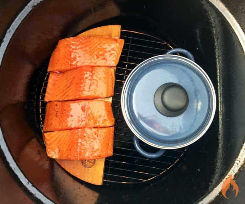 4 salmon filets on cedar plank inside smoker with pot of rice