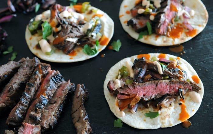 grilled skirt steak tacos on black background