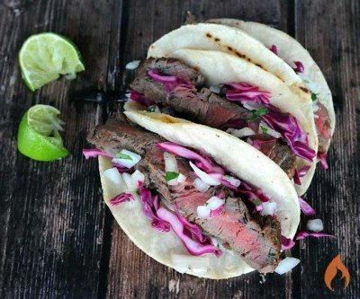 three steak tacos setting on wood with two squeezed limes