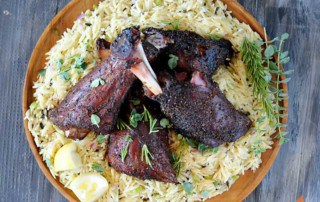 lamb shanks setting on a bed of orzo on a wooden round platter
