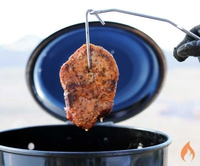 pork chop hanging from a hook above a black barrel grill