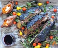 three smoked beef ribs with fresh vegetables on platter with red wine