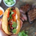 hand holding banh mi sandwich with steak in background