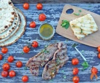 grilled New York Strip steak on a wooden platter with cheese, tomatoes and flatbread