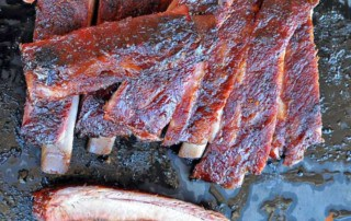 sliced st louis style ribs on a black background with one rib at bottom